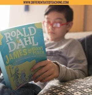 Boy with red glasses reading James and the Giant Peach in bed